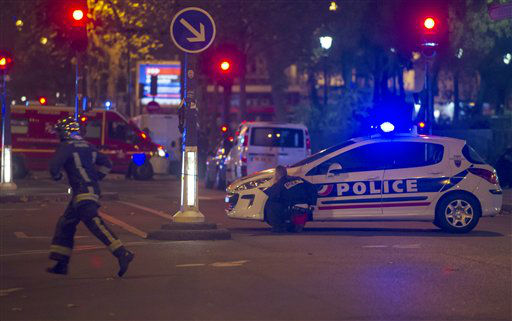 "<div class=""meta image-caption""><div class=""origin-logo origin-image none""><span>none</span></div><span class=""caption-text"">A police officer takes cover behind a car while a rescue worker runs outside the Bataclan theater  in Paris, France (AP Photo/ Kamil Zihnioglu)</span></div>"