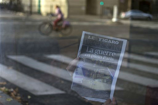 <div class='meta'><div class='origin-logo' data-origin='none'></div><span class='caption-text' data-credit='Peter Dejong'>A man reads a newspaper with a headline reading &#34;War in the heart of Paris&#34; in a hotel lobby in Paris, France, Saturday, Nov. 14, 2015.</span></div>