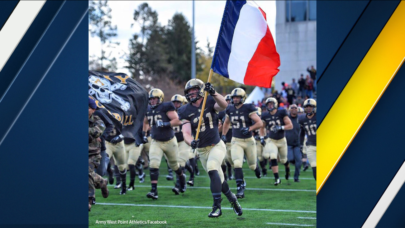 Caleb McNeill of Army carries the French flag onto the football field in West Point, N.Y. one day after terrorists killed more than 120 in Paris.