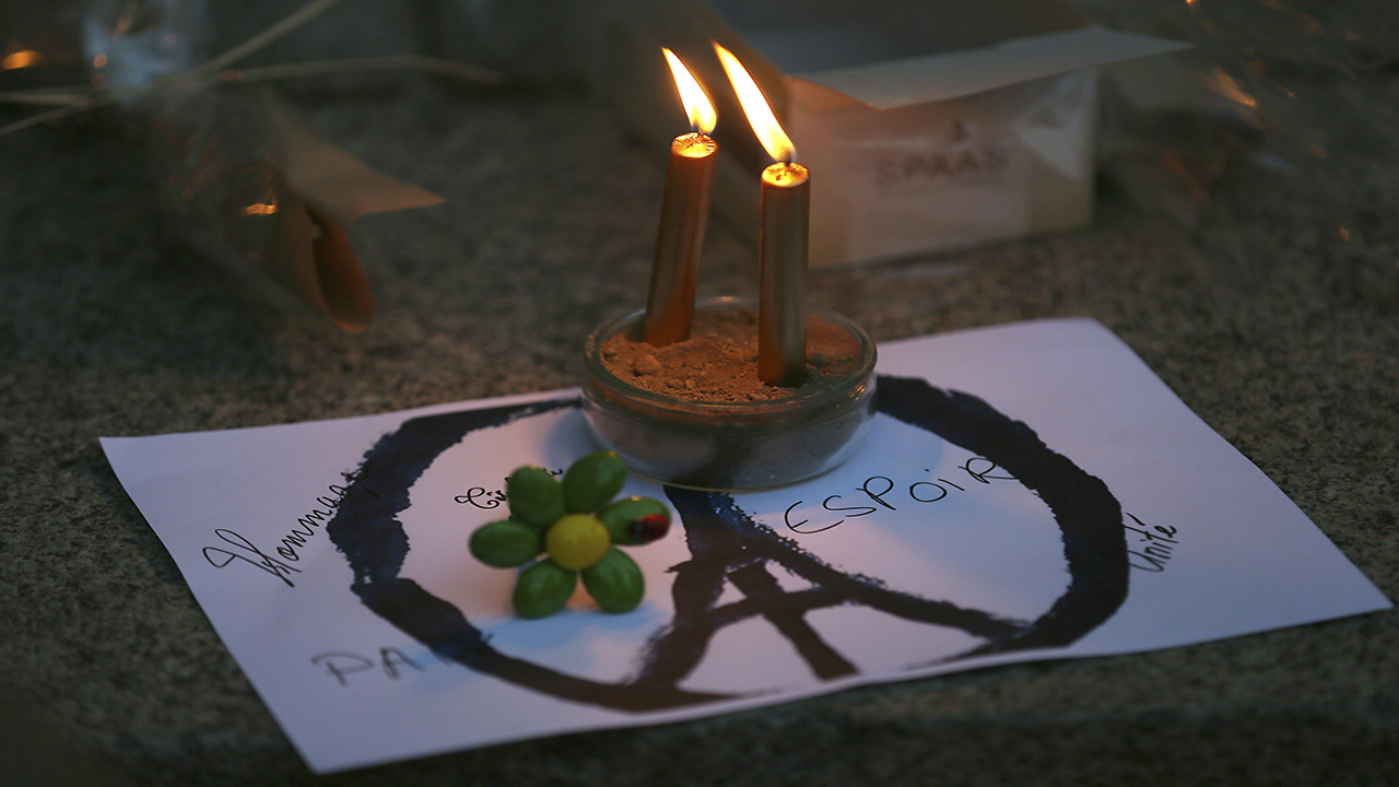 Candles are put on a peace sign combined with the Eiffel Tower at a temporary memorial for the victims of the Paris attacks in Rennes, western France, Saturday, Nov. 14, 2015.