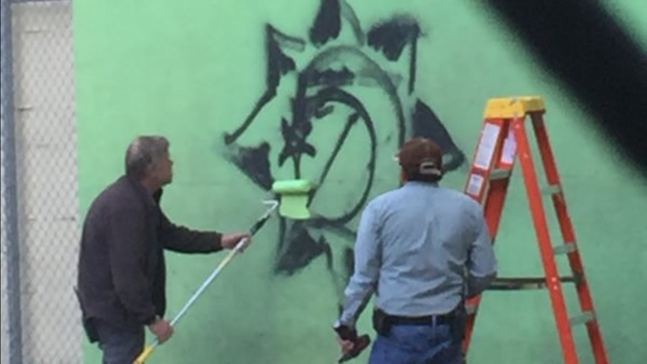In this image, workers paint to cover graffiti at the French American International School in San Francisco, Calif. on Tuesday, November 17, 2015.