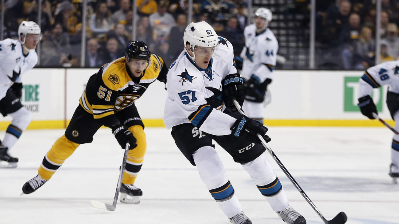 San Jose Sharks' Tommy Wingels (57) brings the puck up in front of Boston Bruins' Ryan Spooner (51) during the first period of an NHL hockey game in Boston, Tuesday, Nov. 17, 2015.