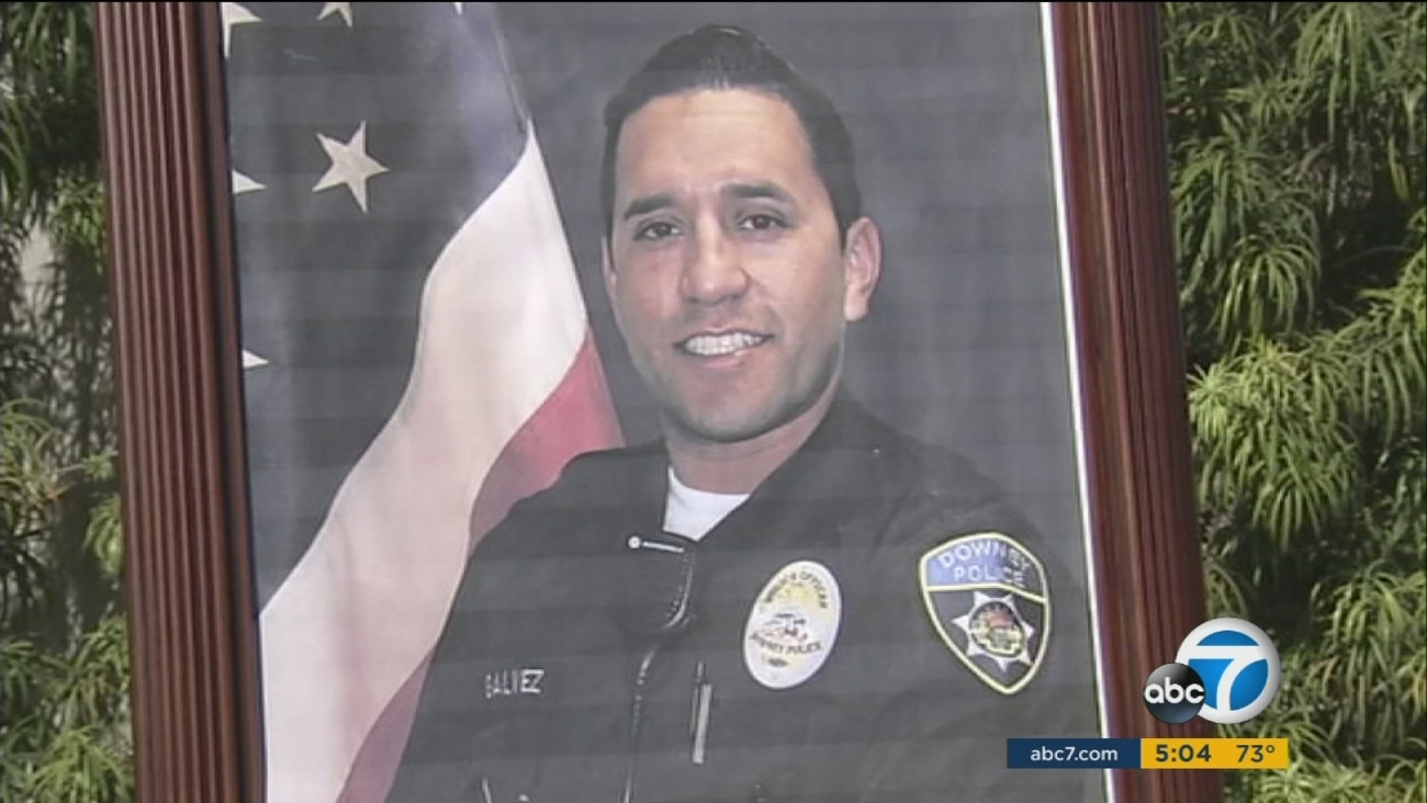 A photo of Ricardo Galvez, 29, a Downey police officer killed in a botched robbery attempt, sits at a memorial set up for him on Thursday, Nov. 19, 2015.