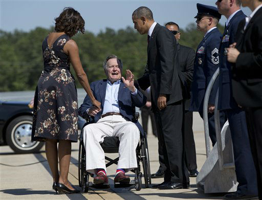 <div class='meta'><div class='origin-logo' data-origin='none'></div><span class='caption-text' data-credit='AP Photo/ Carolyn Kaster'>President Barack Obama and first lady Michelle Obama are greeted by former President George H.W. Bush at George Bush Intercontinental Airport April 9, 2014.</span></div>
