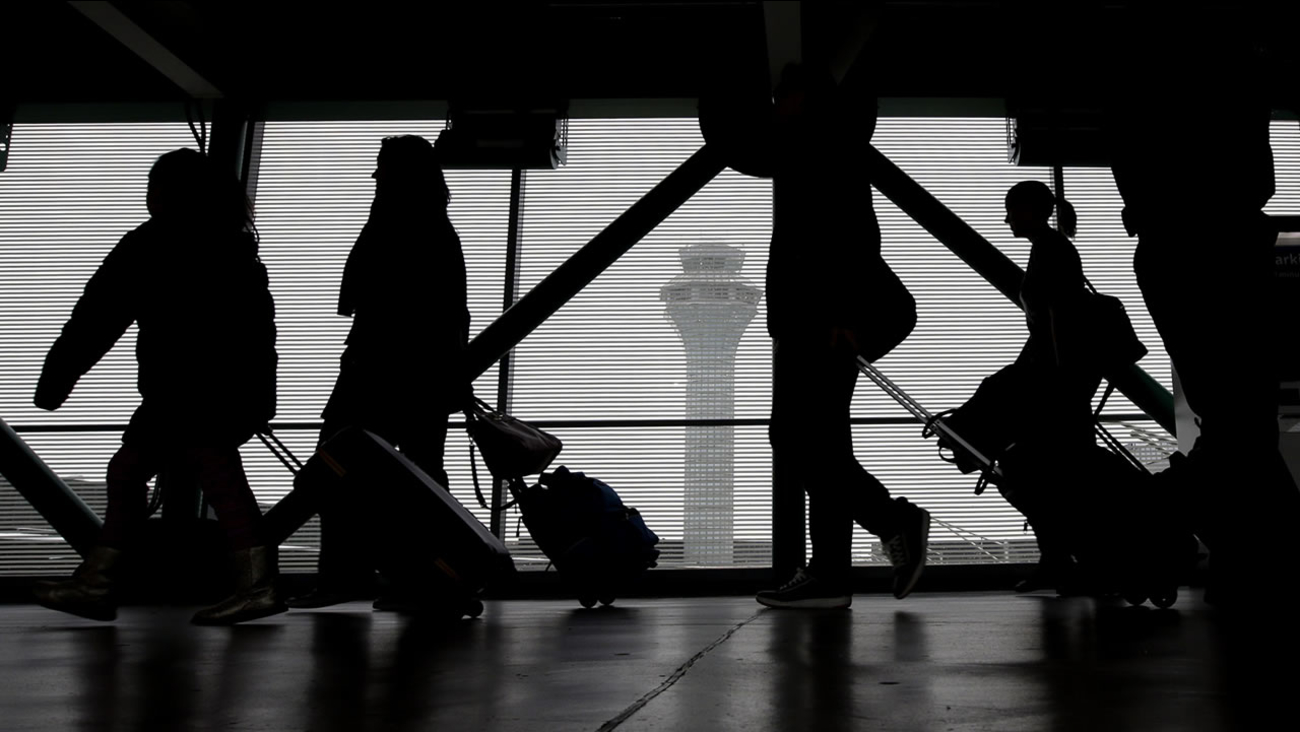 Passengers walk through Terminal 3 at O'Hare International Airport on Saturday, Nov. 21, 2015, in Chicago. (AP Photo/Nam Y. Huh)