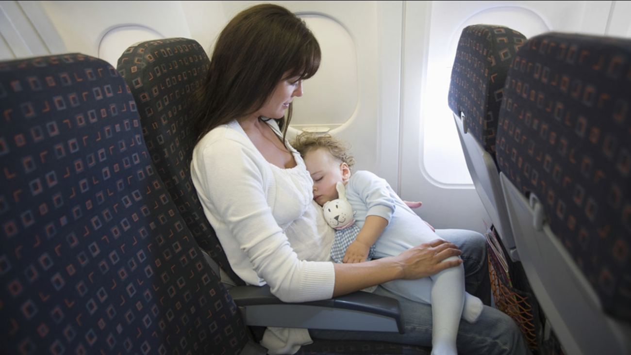 A baby sleeps on mother's lap while in an airplane in this undated file photo.