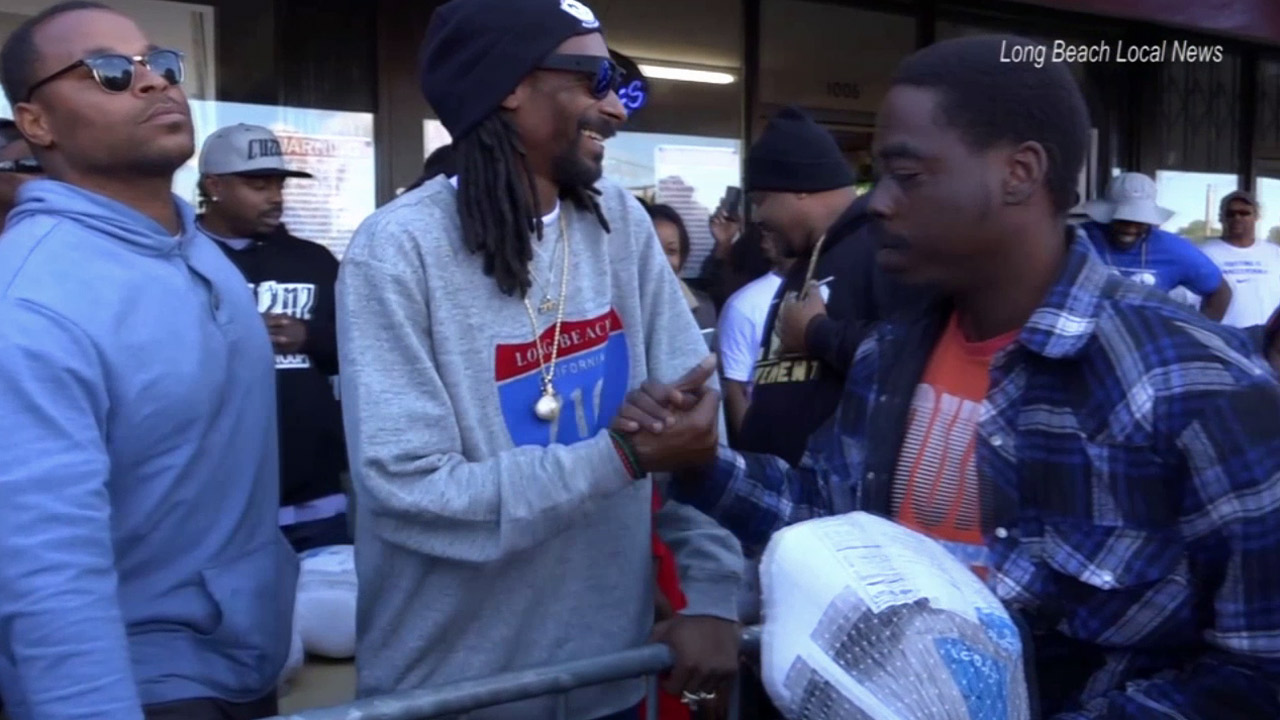 Snoop Dogg says hello to a fan after handing out free turkeys to those in need in Long Beach.