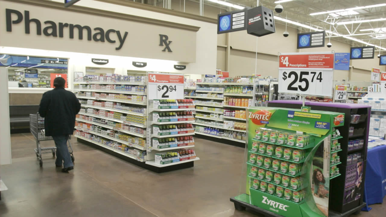 FILE - In this Feb. 20, 2008, file photo, a shopper walks toward the pharmacy at a Little Rock, Ark., Wal-Mart store.