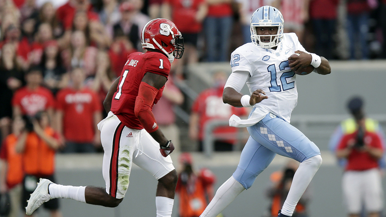 North Carolina quarterback Marquise Williams (12) runs the ball as North Carolina State's Hakim Jones (1) chases during the first half