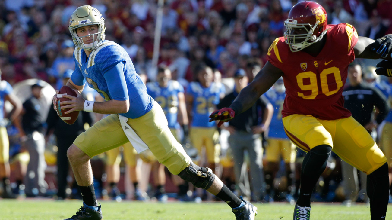 UCLA quarterback Josh Rosen, left, breaks away from Southern California defensive end Claude Pelon during the first half of an NCAA college football game, Saturday, Nov. 28, 2015.