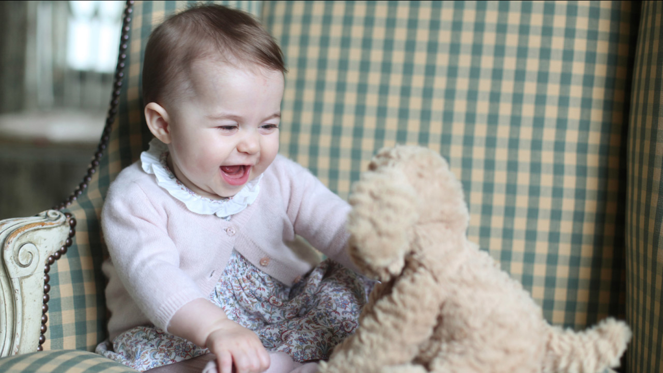 In this undated photo released Sunday Nov. 29, 2015, by Britain's Duke and Duchess of Cambridge, showing Princess Charlotte with her cuddly toy dog, at Anmer Hall in England.