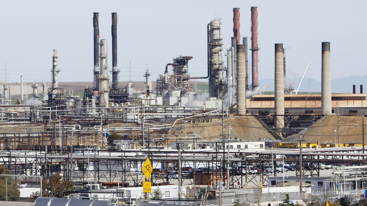 This March 9, 2010 file photo shows a tanker truck passing the Chevron oil refinery in Richmond, Calif. Chevron Corp.
