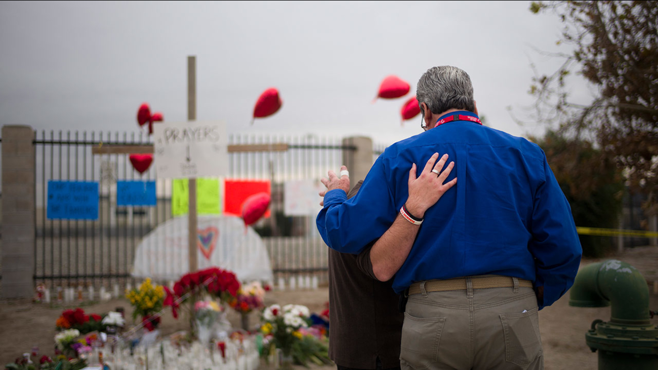 Chaplain Chuck Bender, right, prays with Michael Davila at a makeshift memorial honoring the victims of Wednesday's shooting rampage, Friday, Dec. 4, 2015, in San Bernardino.