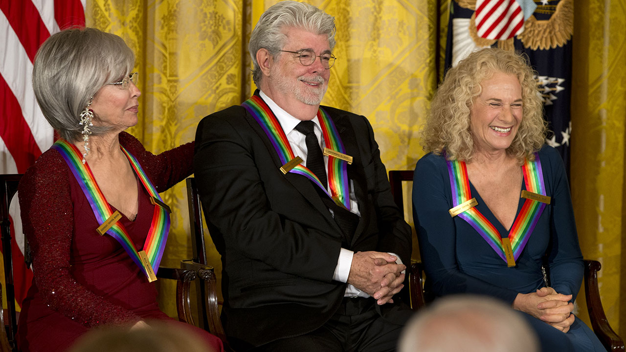 2015 Kennedy Center Honors honorees from left, actress and singer Rita Moreno, filmmaker George Lucas, and singer-songwriter Carole King, react as President Barack Obama speaks