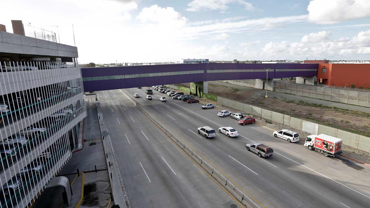 Vehicles pass under a walking bridge that connects the new Cross Border Xpress air terminal in San Diego, right, to the Tijuana International Airport, left.