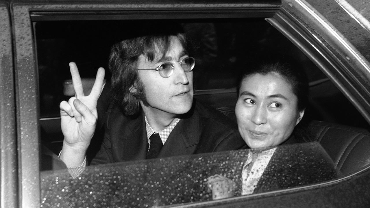 Former Beatle John Lennon, left, and his wife Yoko Ono, leave the Immigration and Naturalization Service, at 20 West Broadway, March 16, 1972, New York. (AP Photo/Anthony Camerano)