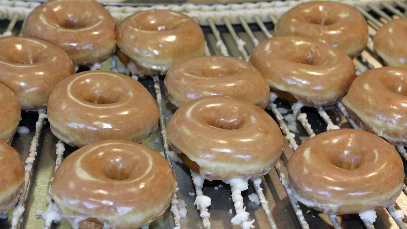 Glazed doughnuts roll by on a conveyer belt at a Krispy Kreme store in Charlotte, N.C., Thursday, Dec. 6, 2007. (AP Photo/Chuck Burton)