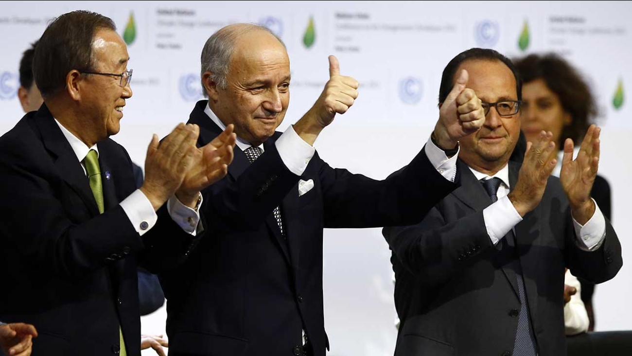 French foreign minister Laurent Fabius, center, applauds with UN Secretary General Ban Ki-moon, left, and French President Francois Hiolland after the final conference of  COP21
