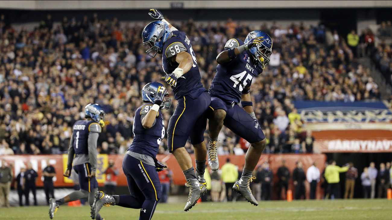 Navy linebacker Daniel Gonzales (58) and linebacker D.J. Palmore (45) react after Army missed a field goal during the second half