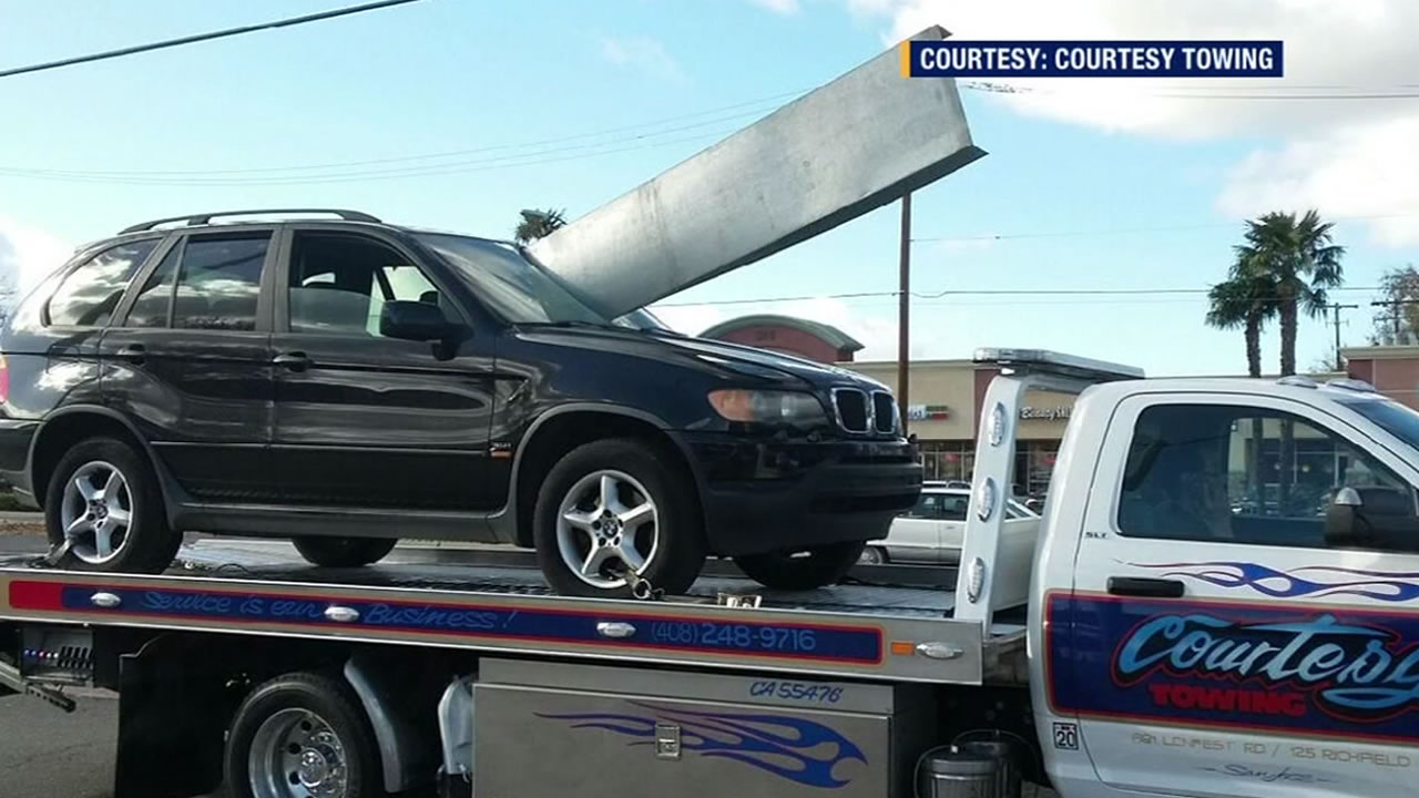 A black SUV is seen mounted on top of a tow truck with a metal beam pierced through the windshield in this undated image.