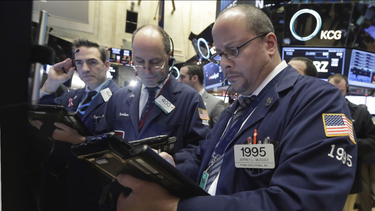 Jeffrey Vazquez, right, works with fellow traders on the floor of the New York Stock Exchange, Wednesday, Dec. 16, 2015. Stocks are opening higher, led by gains in banking shares ahead of an interest rate decision by the Federal Reserve.
