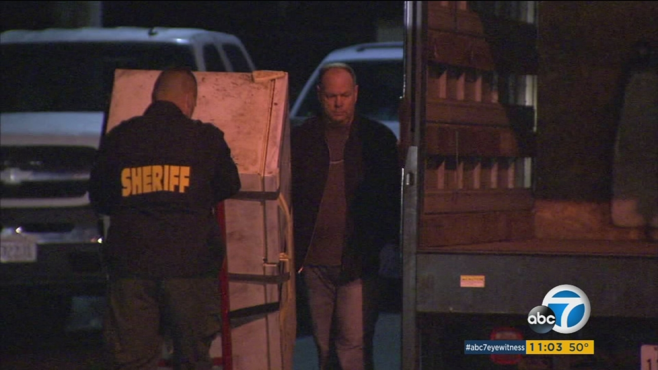 Investigators remove a refrigerator police said the remains of a woman were found in at a Santa Ana home on Thursday, Dec. 17, 2015.