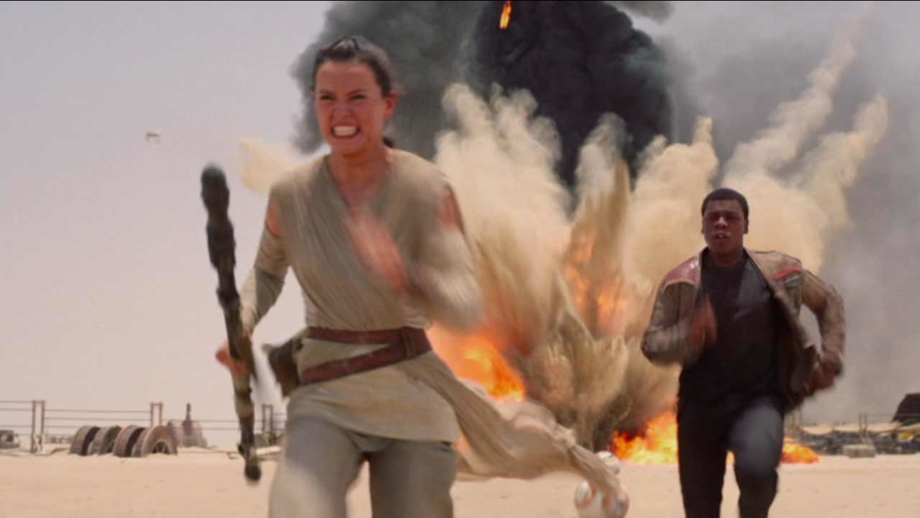 This photo provided by Disney/Lucasfilm shows Daisy Ridley, left, as Rey, and John Boyega, right, as Finn, in a scene from the film, 'Star Wars: The Force Awakens.'
