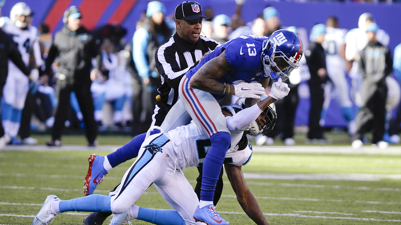 A referee separates New York Giants wide receiver Odell Beckham (13) and Carolina Panthers' Josh Norman (24) during the first half of an NFL football game Sunday, Dec. 20, 2015
