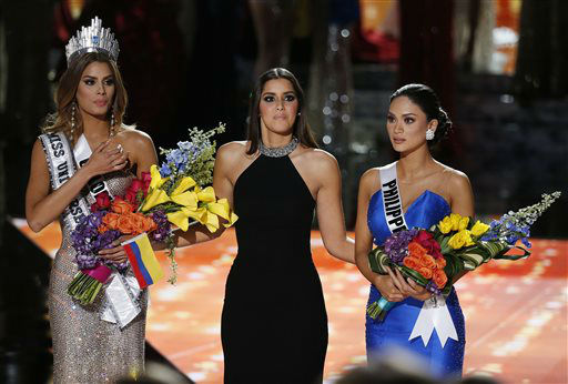 <div class='meta'><div class='origin-logo' data-origin='none'></div><span class='caption-text' data-credit='AP Photo/ John Locher'>Former Miss Universe Paulina Vega, center, reacts before taking away the flowers, crown and sash from Miss Colombia Ariadna Gutierrez</span></div>