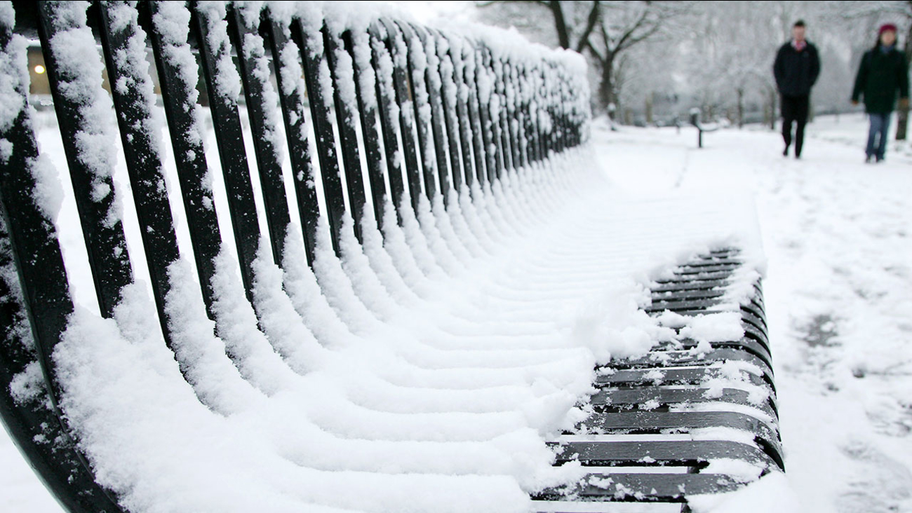 People walk pass a snow covered bench in a park