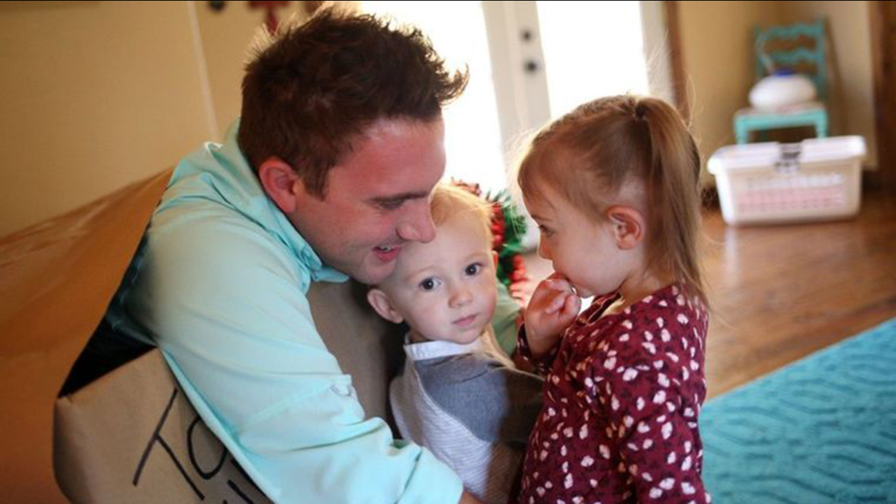 Petty Officer Second Class Ryan Dodd embraces his children, Willow and Liam, after a surprise reunion on Friday