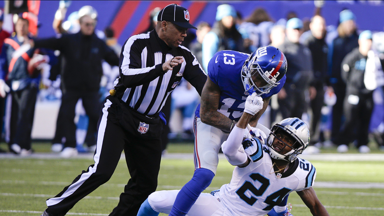 A referee, left, separates New York Giants wide receiver Odell Beckham (13) and Carolina Panthers' Josh Norman (24) during the first half of an NFL football game Sunday, Dec. 20