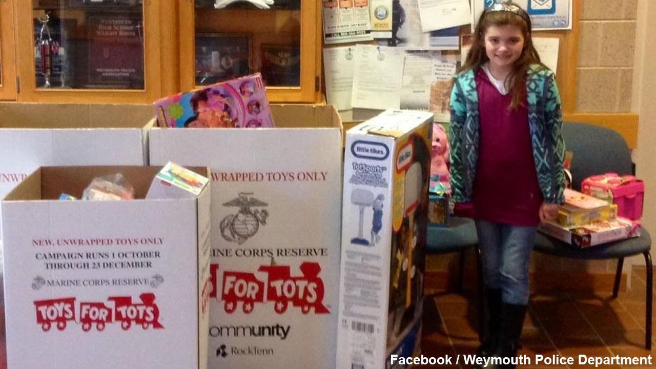 Sivana Athanas, 9, poses alongside toys she donated to Toys for Tots.
