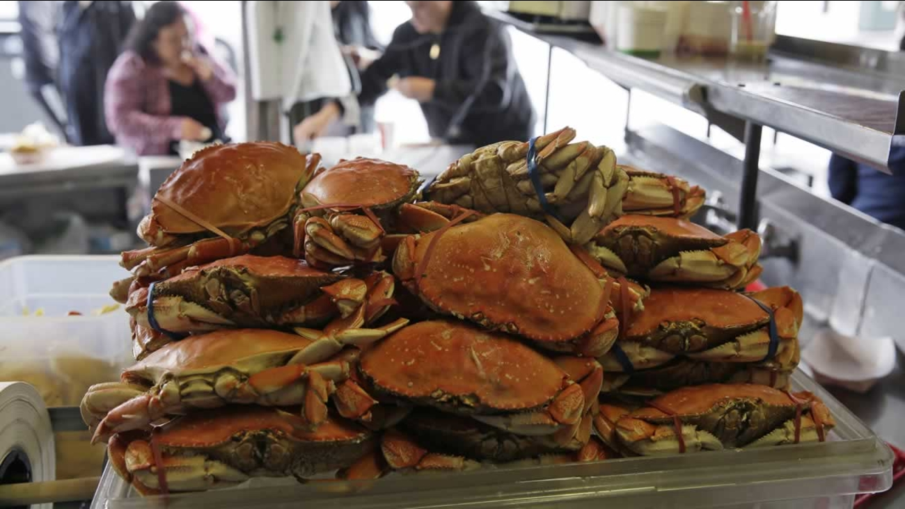 A stack of imported Dungeness crabs are shown for sale as people eat them in the background at Fisherman's Wharf Tuesday, Dec. 22, 2015, in San Francisco.