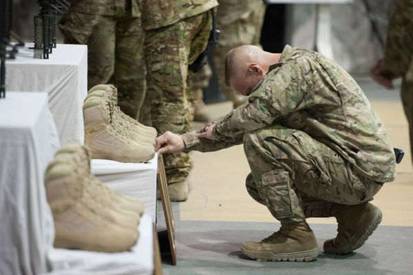 """<div class=""""meta image-caption""""><div class=""""origin-logo origin-image none""""><span>none</span></div><span class=""""caption-text"""">Chief Master Sgt. Matt Grengs, 455th Air Expeditionary Wing command chief, pays his respects during a fallen comrade ceremony at Bagram Air Field, Afghanistan, Dec. 23, 2015. (Photo/Tech. Sgt. Robert Cloys)</span></div>"""