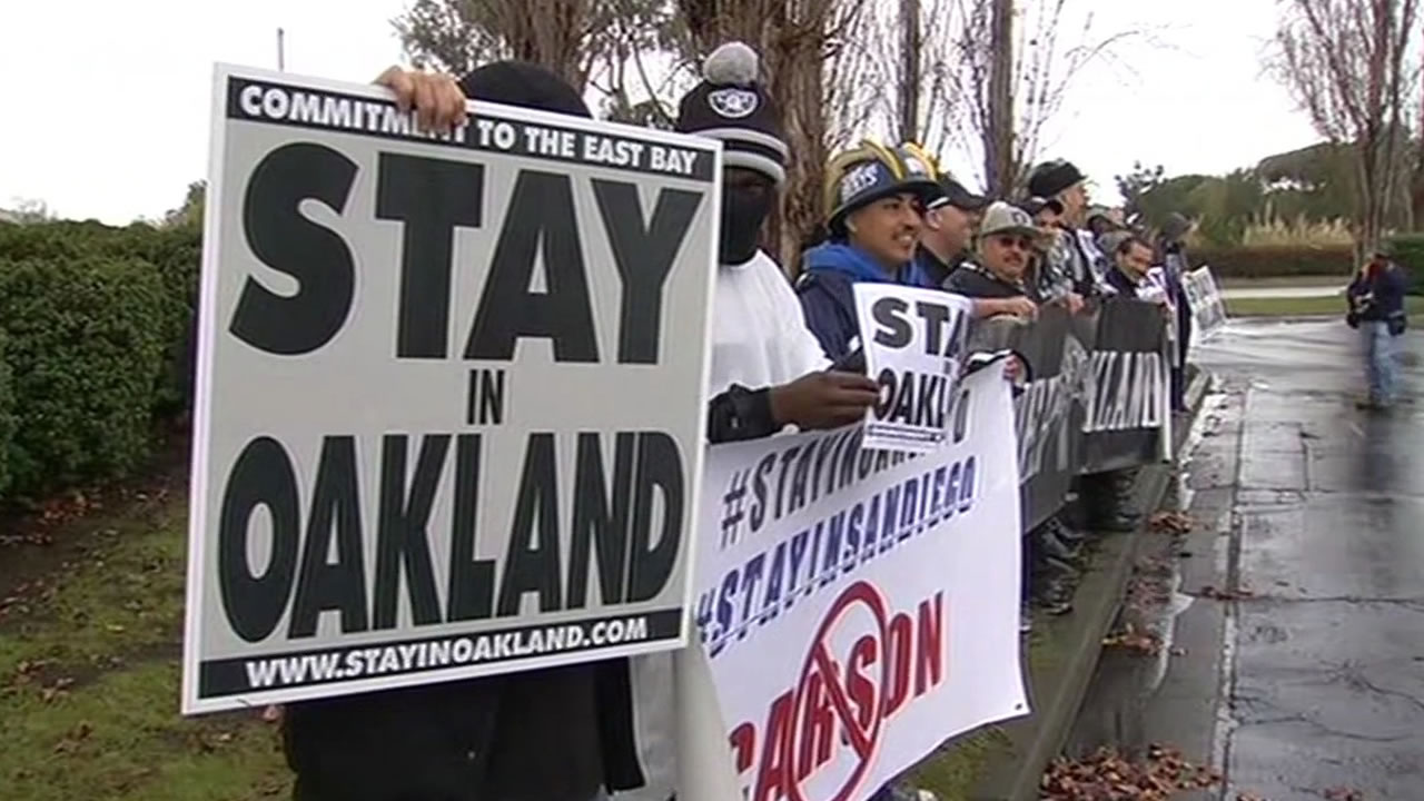 "Oakland Raiders hold signs saying ""stay in Oakland"""