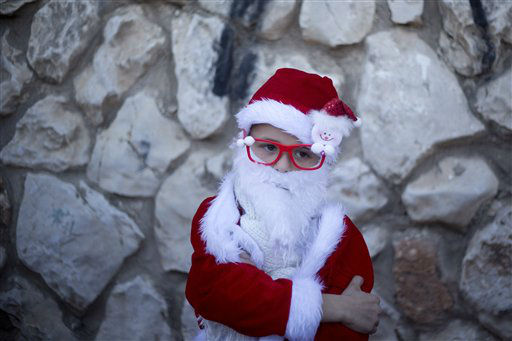 "<div class=""meta image-caption""><div class=""origin-logo origin-image none""><span>none</span></div><span class=""caption-text"">An Israeli Arab Christian boy dressed up as Santa Claus waits for the start of the annual Christmas parade in in the northern Israeli city of Nazareth, Israel. (AP Photo/ Ariel Schalit)</span></div>"