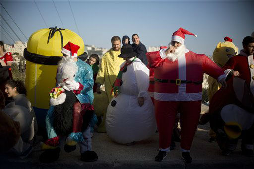 "<div class=""meta image-caption""><div class=""origin-logo origin-image none""><span>none</span></div><span class=""caption-text"">Israeli Arab Christians, one dressed up as Santa Claus, wait for the start of the annual Christmas parade in in the northern Israeli city of Nazareth, Israel. (AP Photo/ Ariel Schalit)</span></div>"