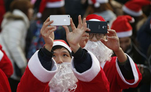 "<div class=""meta image-caption""><div class=""origin-logo origin-image none""><span>none</span></div><span class=""caption-text"">Volunteers clad in Santa Claus costumes takes photos during a Christmas charity event as they gather to deliver gifts for the poor in downtown Seoul, South Korea. (AP Photo/ Lee Jin-man)</span></div>"