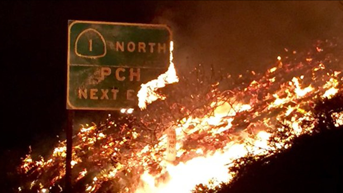 A sign for the Pacific Coast Highway near Solimar Beach burns near Ventura on Saturday, Dec. 26, 2015.