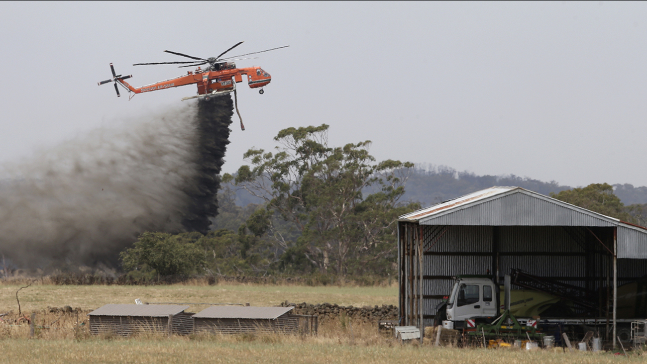 A Skycrane helicopter drops a load of water as it works to hold back a wildfire from the hamlet of Claredon in Victoria, Australia.