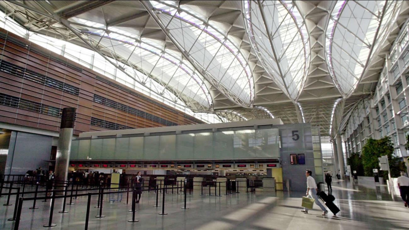 passenger walks in a nearly empty international terminal at SFO