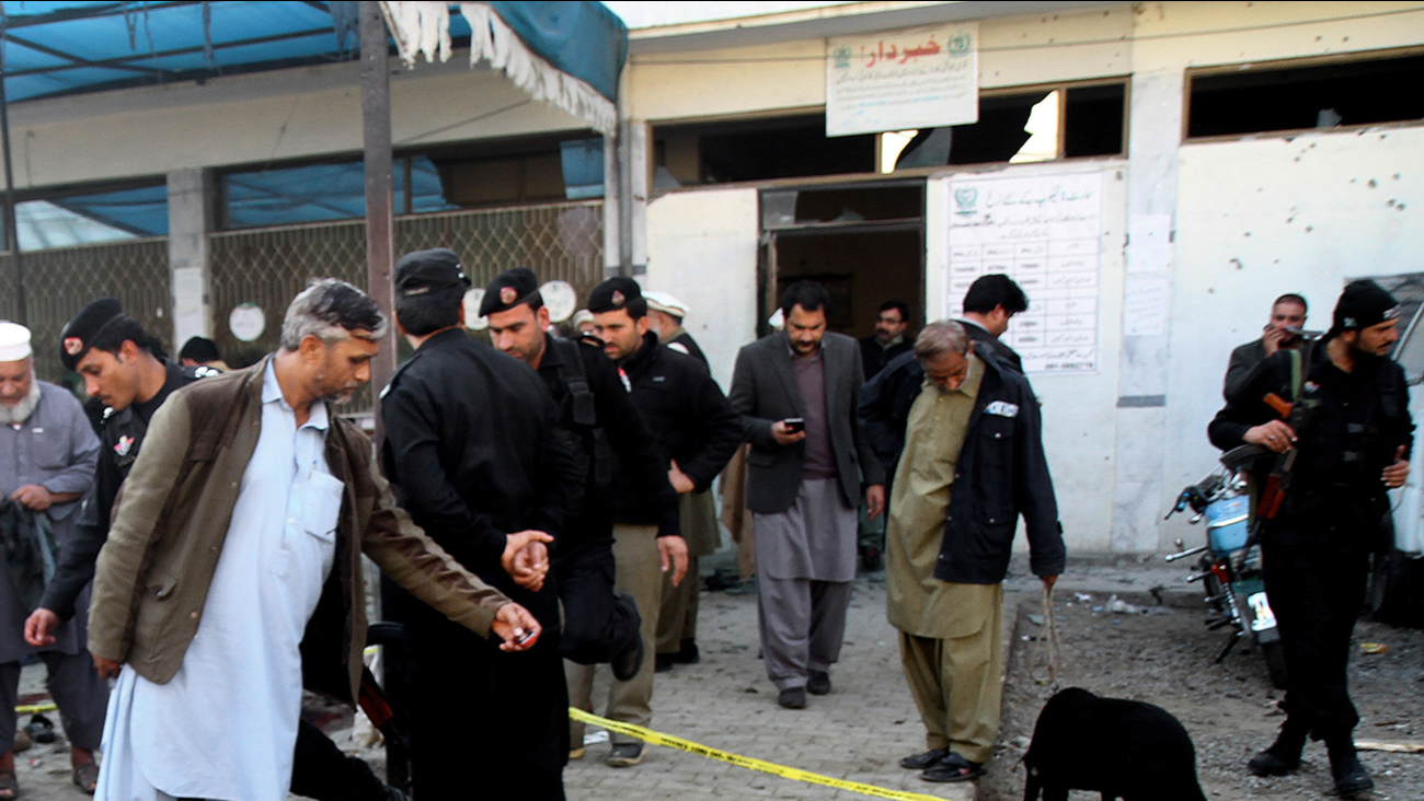 Pakistani security officials examine the site of a suicide attack in Mardan, Pakistan, Tuesday, Dec. 29, 2015.