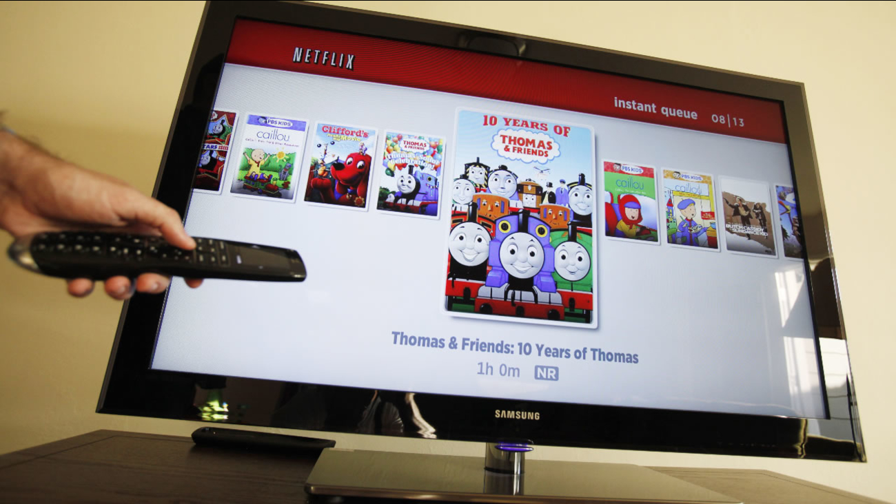 FILE - In this July 20, 2010 file photo, a Netflix customer looks for a movie on Netflix in Palo Alto, Calif.
