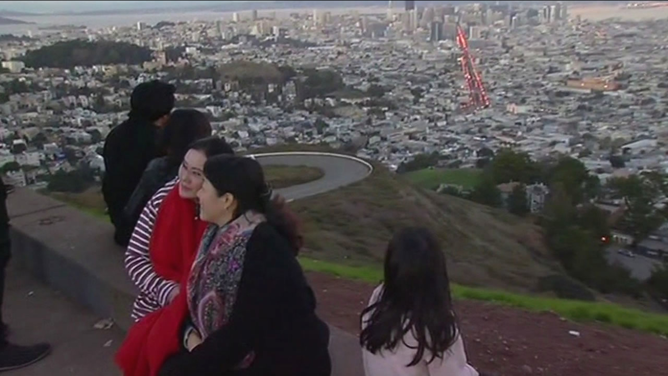This image from Tuesday, December 29, 2015 shows tourists posing for photos at San Francisco's Twin Peaks.