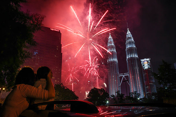 <div class='meta'><div class='origin-logo' data-origin='none'></div><span class='caption-text' data-credit='AP Photo/Joshua Paul'>A Malaysian woman covers her child's ears while watching fireworks display in front of Malaysia's landmark building, Petronas Twin Towers on Jan. 1.</span></div>