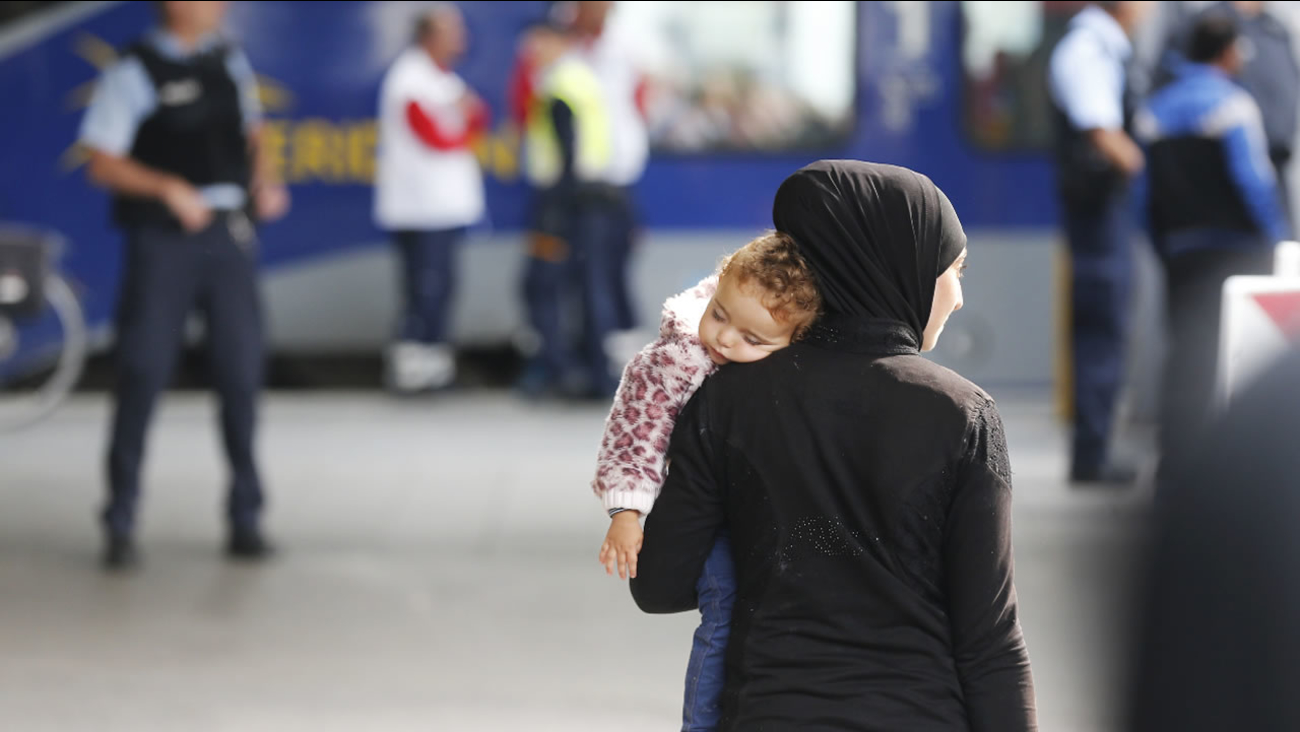 A migrant carries her child as they arrive at the main train station in Munich, Germany, Saturday, Sept. 5, 2015.