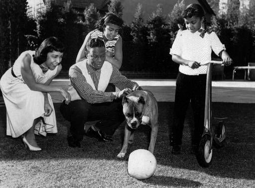"""<div class=""""meta image-caption""""><div class=""""origin-logo origin-image none""""><span>none</span></div><span class=""""caption-text"""">The family of Nat """"King"""" Cole poses for a family picture in 1957.  Nat's wife, Maria and daughters Carol, 12 and Natalie, 6, right, watch their boxer, Mr. Pet.  (AP Photo) (AP Photo/ COLIN CRAWFORD)</span></div>"""