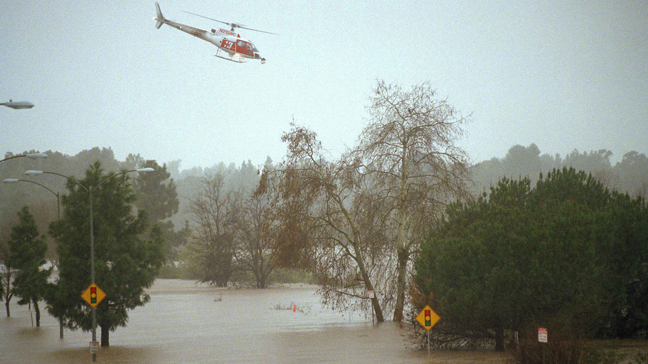 A Los Angeles County fire department helicopter flies over a flooded street in Burbank, searching for possible stranded motorists, Tuesday, Feb. 3, 1998 following El Nino storms.
