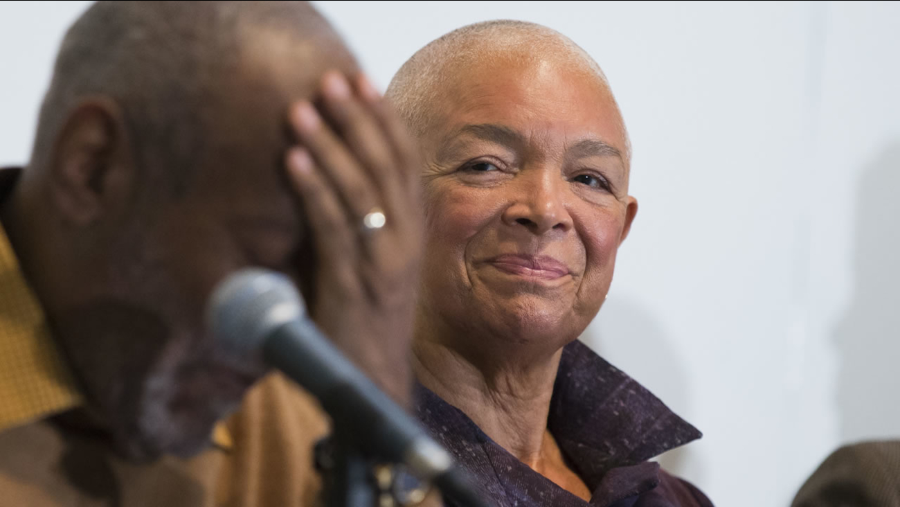 In this Nov. 6, 2014 file photo, Camille Cosby, right, looks on as Bill Cosby speaks during a news conference